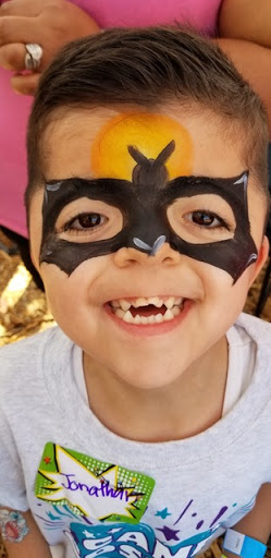 Smiling boy with batman facepaint; patient of Fresh Start Surgical Gifts Med Spa Growth & Profitability donations