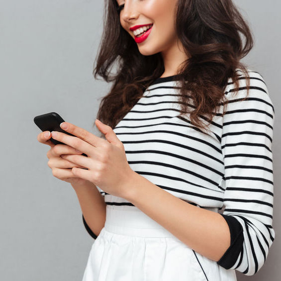 Cropped image of smiling woman in a black and white striped shirt looking at her phone happy about happy Medical Spa Social Media Management