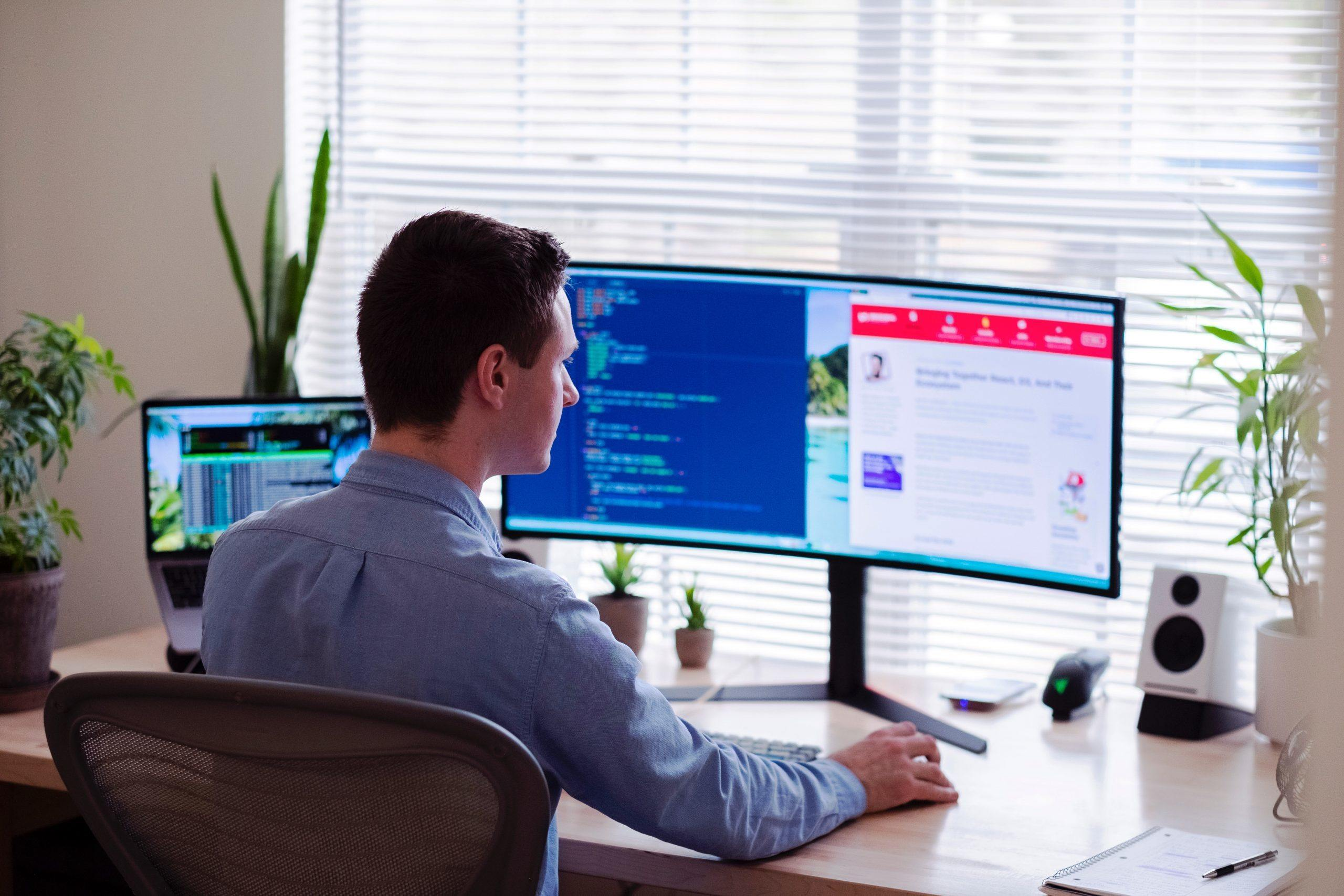 Man wearing a collard shirt  sitting at computer looking for 9 Best Software and Tools for Telemedicine